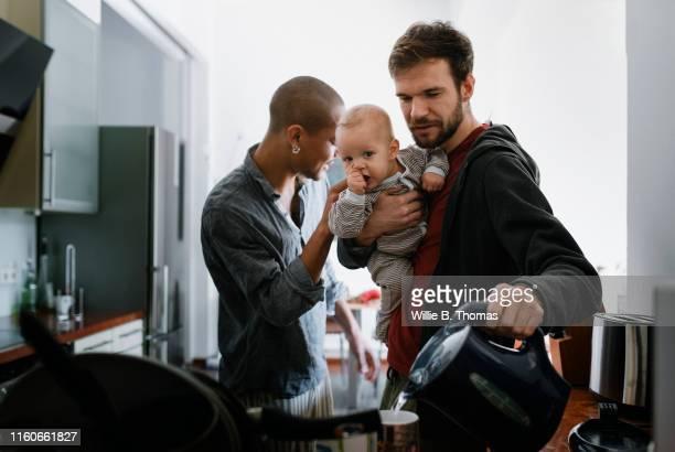 gay father multitasking with baby - etwas herstellen stock-fotos und bilder