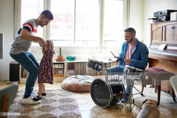 gay fathers playing drums and teaching daughter to dance - drum kit stock pictures, royalty-free photos & images