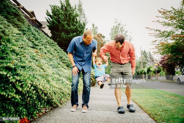 Gay fathers playing with baby son on sidewalk