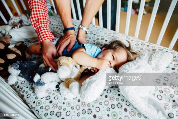gay fathers tickling baby son in crib - tickling stock pictures, royalty-free photos & images