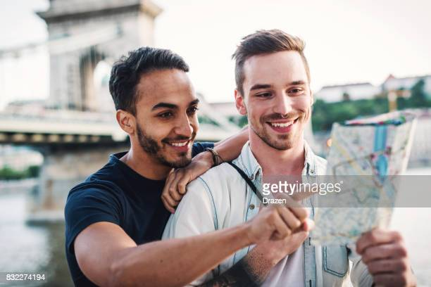 Gay guys exploring map near famous landmark in Budapest
