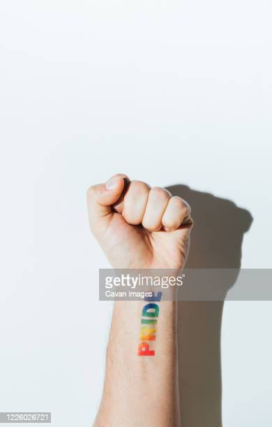 gay guy's hand with a tattoo that says pride and nail polish. - bisexuality fotografías e imágenes de stock