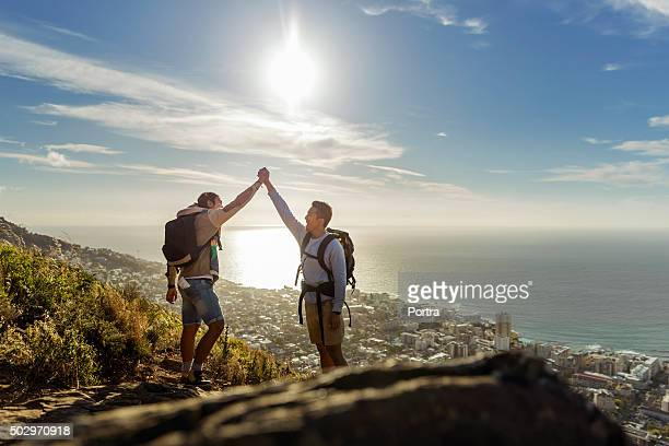 Gay hikers celebrating success on hill