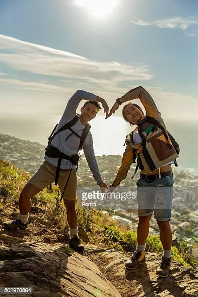 Gay escursionisti formano un cuore forma con le mani sulle rocce