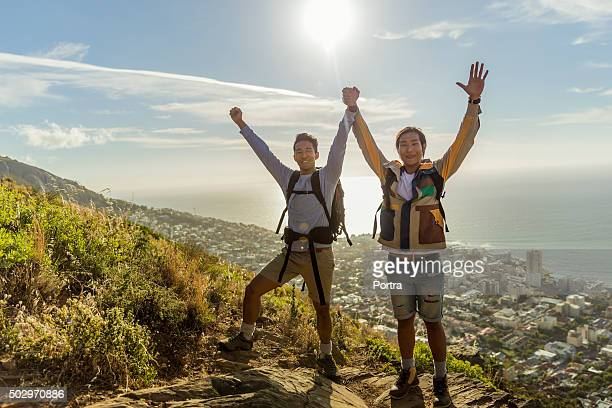 Gay hikers raising hands on hill against sky