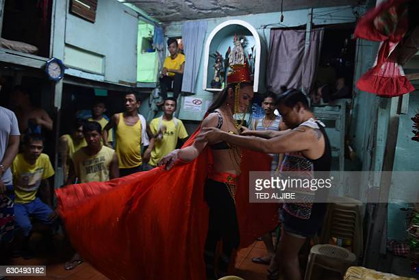 Gay inmate is helped to get dressed prior to a mock Miss Universe pageant inside a prison in Manila on December 24, 2016 Inmates dressed as beauty...