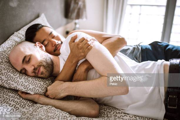 gay love - abbracciarsi a letto foto e immagini stock