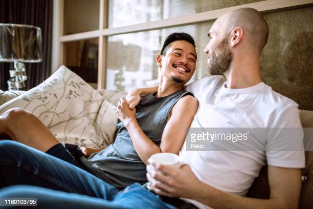 gay lovers watching tv in the living room - gay couple stock pictures, royalty-free photos & images