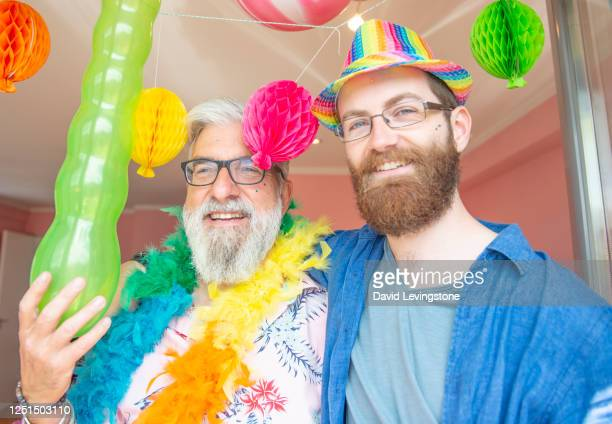 gay male couple celebrating gay pride at home - equality stock pictures, royalty-free photos & images