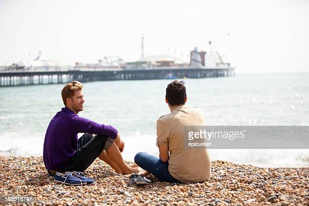 Gay male couple sitting on the beach in Brighton