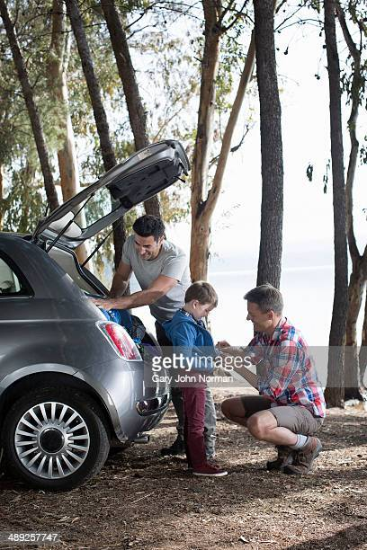 Gay male couple with their son,packing the car