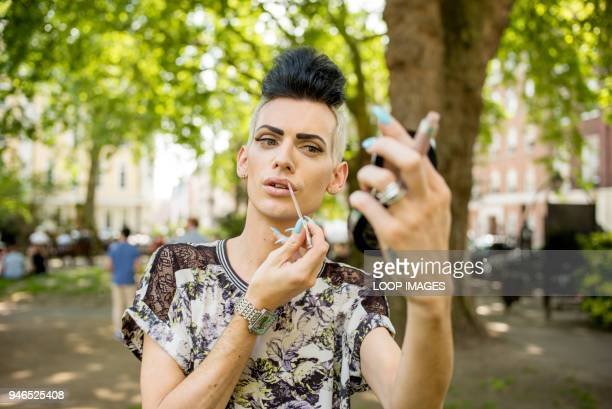 a gay man applies his make up - gay man stock pictures, royalty-free photos & images