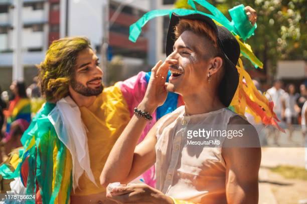 hombre gay aplicando brillo en su cara - homofobia fotografías e imágenes de stock