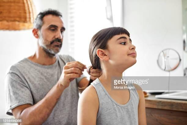 de vrolijke mens bindt het haar van de dochter in badkamers - alleenstaande vader stockfoto's en -beelden