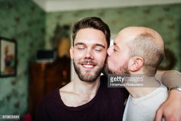 Gay Man Kissing His Partner On The Cheek