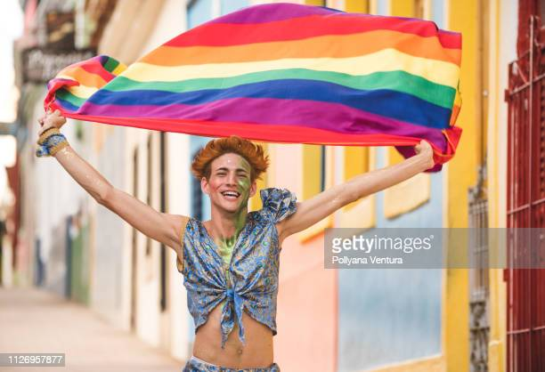 gay man running holding rainbow flag - the americas stock pictures, royalty-free photos & images