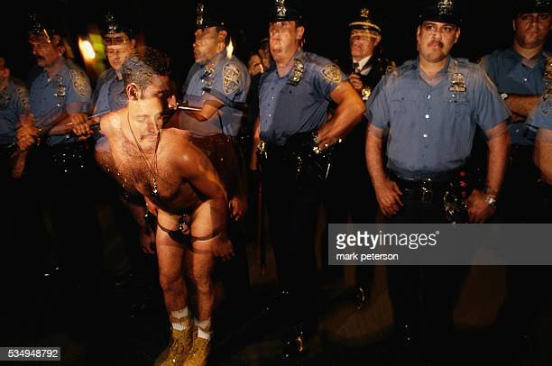 A gay man strips in front of a row of police officers during the twentyfifth anniversary celebration of the Stonewall Uprising On June 26 1969 gay...