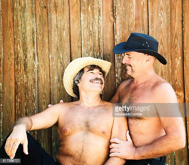 gay mature bear hairy couple smiling at each other - hairy man chest stock photos and pictures
