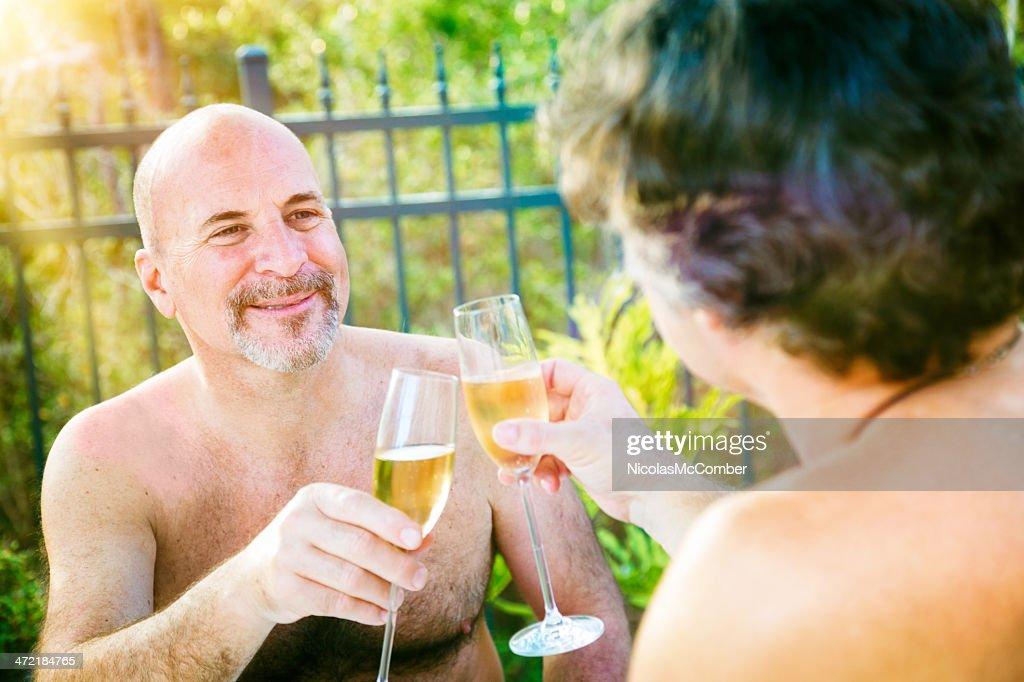 Gay mature nudist men toasting outside : Stock Photo