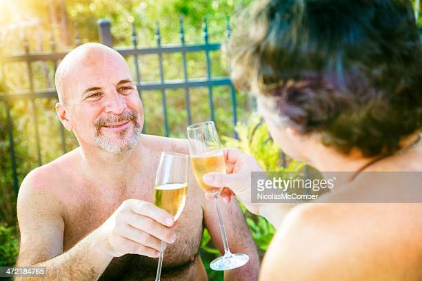 Gay mature nudist men toasting outside