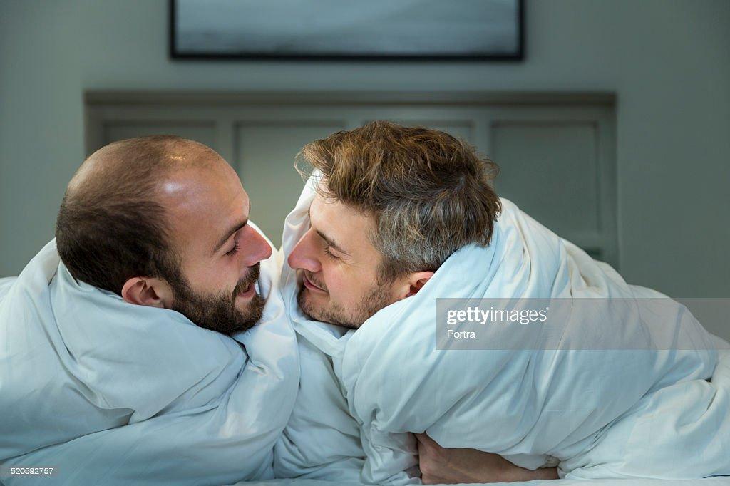 Gay men kissing in bed
