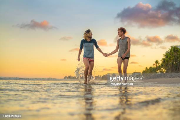gay men couple running hand in hand at sunset on tropical beach - gay men swimwear stock pictures, royalty-free photos & images