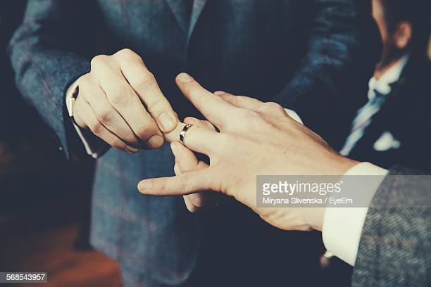 gay men exchanging rings at wedding ceremony - man holding engagement ring stock photos and pictures