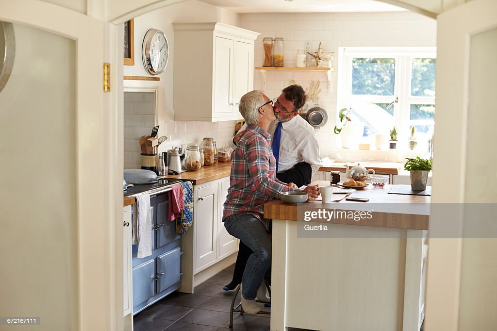 Gay Men Kissing In Kitchen Before Work, Full Length : Stock Photo