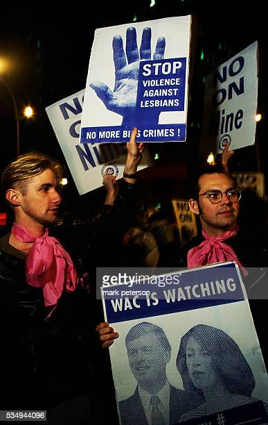 Gay men participate in an antigay bashing demonstration through the East Village They carry Women's Action Coalition signs decorated with photographs...