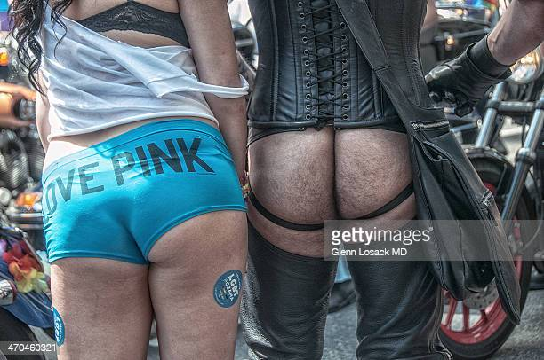 Gay Parade Manhattan 2013. Only the backsides of 2 participants in the parade. One man showing only his buttocks dressed in black leather. Woman...
