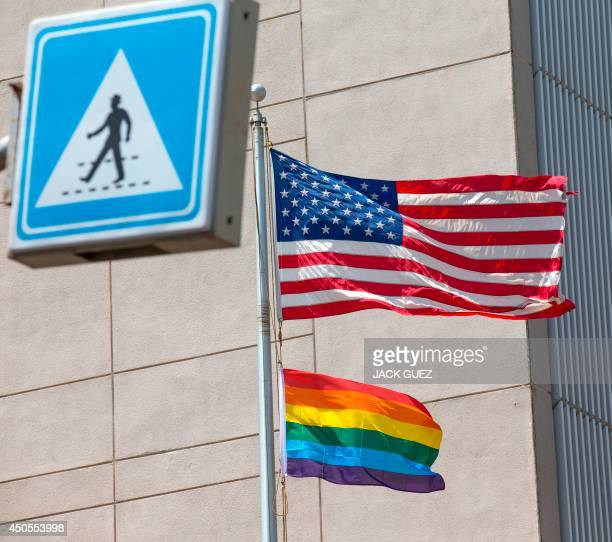 A gay pride flag is raised next to the US flag is at the US embassy in the vicinity of the annual gay pride parade in the Israeli coastal city of Tel...