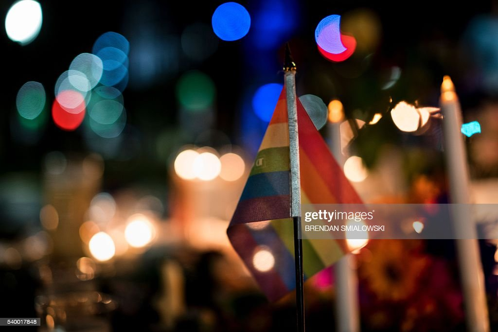 TOPSHOT - A gay pride flag is seen at a memorial after a vigil outside the Dr. Phillips Center for the Performing Arts for the mass shooting victims at the Pulse nightclub June 13, 2016 in Orlando, Florida. The American gunman who launched a murderous assault on a gay nightclub in Orlando was radicalized by Islamist propaganda, officials said Monday, as they grappled with the worst terror attack on US soil since 9/11. / AFP / Brendan Smialowski
