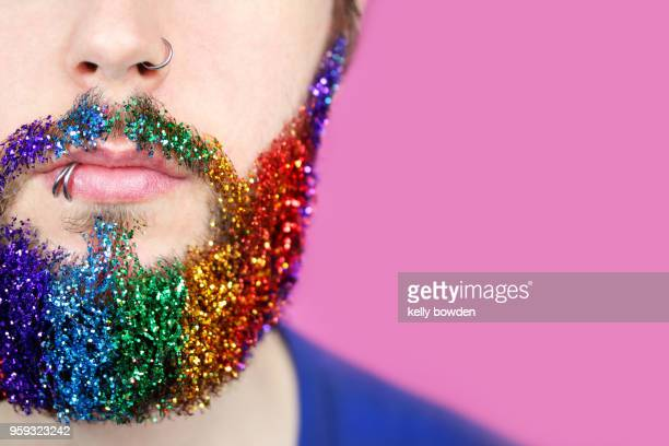 gay pride man with rainbow glitter beard - barba peluria del viso foto e immagini stock