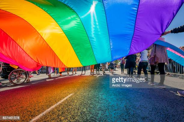 gay pride parade-people marching with a large flag, reykjavik, iceland - lgbt - fotografias e filmes do acervo