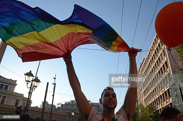 Gay Pride participant waves a rainbow colored flag in the air Hundreds of people on Saturday joined Greece's annual gay pride parade in a...