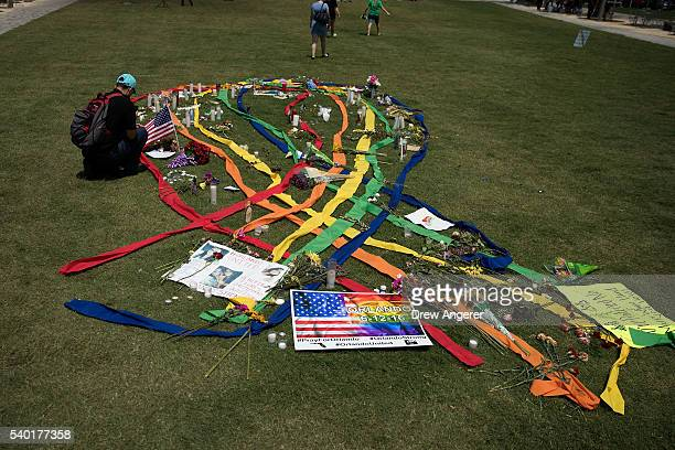 A gay pride ribbon is displayed on the lawn of the Dr Phillips Performing Arts Center near a makeshift memorial for the victims of the Pulse...