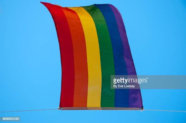 A Gay Rainbow Flag against a blue sky