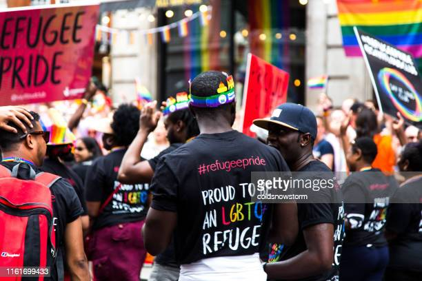 gay refugees celebrating at gay pride parade on streets of central london, uk - refugee stock pictures, royalty-free photos & images