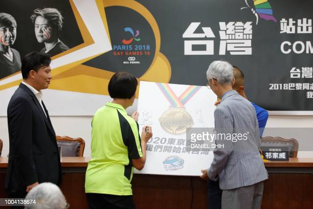 Gay rights activist Chi Chiawei accompanied by lawmaker Huang Kuochang signs a referendum for Taiwan to compete in the Tokyo 2020 Olympics Games...