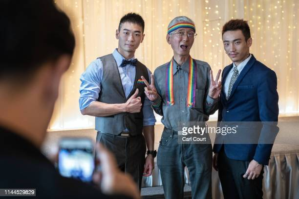Gay rights activist Chi Chiawei poses for a photograph with two gay men during a wedding event to raise HIV awareness a day after Taiwan's parliament...