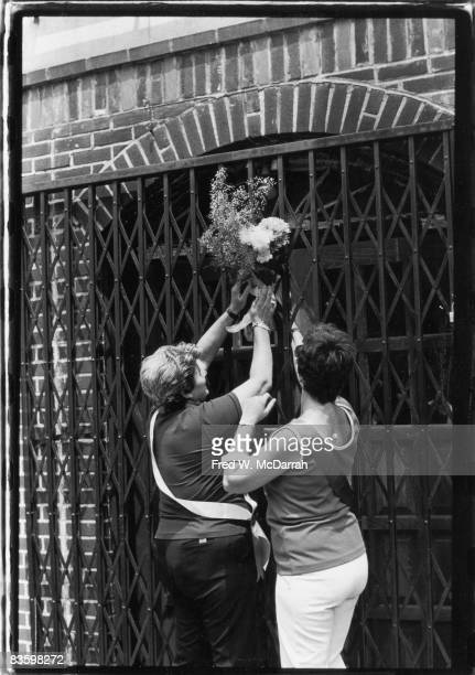 Gay Rights activist 'Mama' Jean Devente and an unidentified woman attach a bunch of flowers to the closed gate of the building that formerly housed...