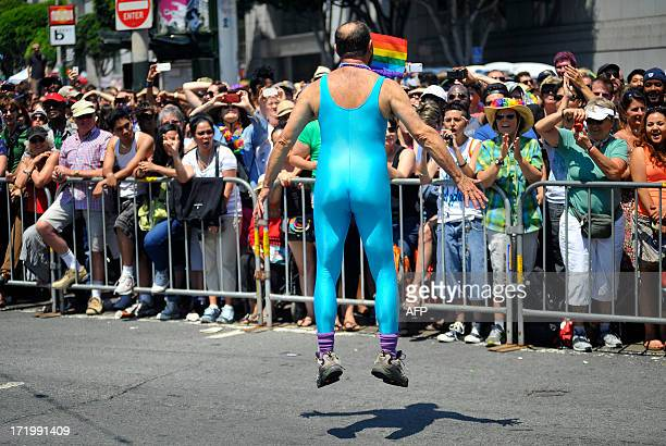 A gay rights supporter jumps with excitement along the parade route at San Francisco's Gay Pride festival on June 2013 AFP PHOTO/JOSH EDELSON