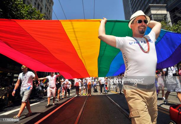Gay rights supporters carry a rainbow flag along the parade route at San Francisco's Gay Pride festival in California on Sunday June 2013 AFP Photo /...