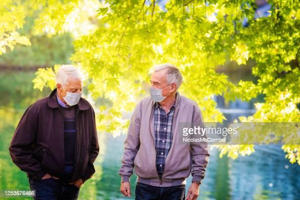 couples masculins aînés gais utilisant des masques protecteurs pendant la promenade d'automne dans le parc - gay seniors photos et images de collection