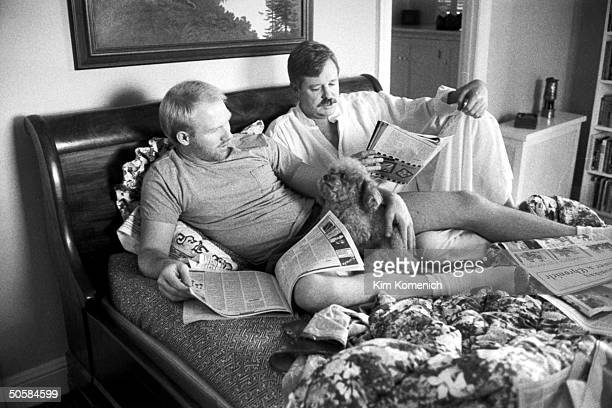 Gay writer Armistead Maupin reading on bed w lover Terry Anderson HIVpositive whose AIDS is under control w AZT w their dog Willie