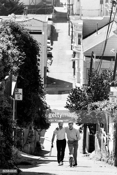 Gay writer Armistead Maupin walking w arm around lover Terry Anderson who tests HIVpositive is taking AZT seen walking their dog Willie