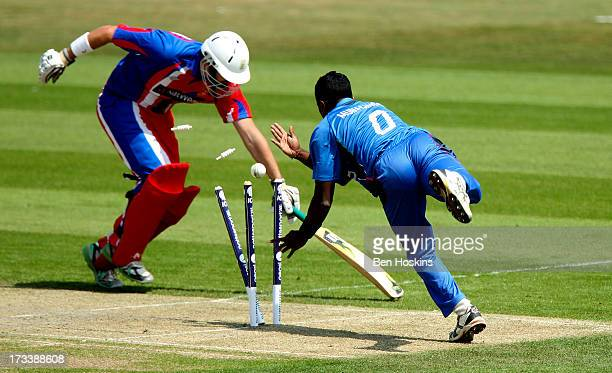 Gayashan Munasinghe of Italy attempts to run out Alexander Cooke of Jersey during the semi final match between Italy and Jersey at the ICC European...