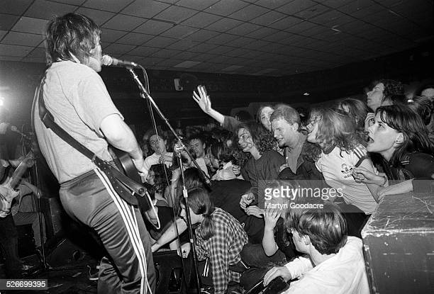 Gaz Coombes of Supergrass performs on stage, showing Britpop fans reaching out from the front rows of the audience, at Moles Club, Bath, United...
