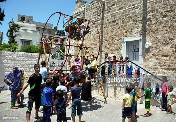 Gazaian Muslims sheltering at the Greek Orthodox Church try to make the most of their Eid alFitr celebrations on July 2014 During normal times...