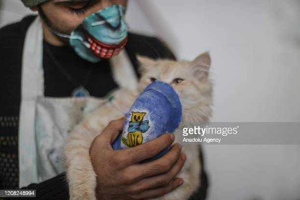 Gazan artist wears a face mask to raise awareness to the novel coronavirus spread holds a cat in Gaza Strip on March 25 2020